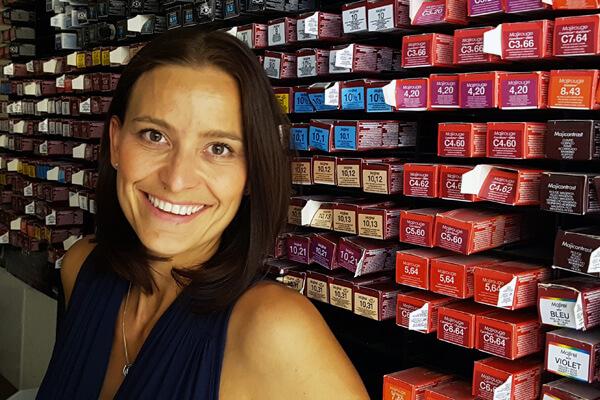Porträt Monique Jahn. Inhaberin pro kopf style GmbH. Hintergrund: Friseurfarben.